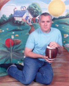 Photo of RM Vaughan holding a football in front of a painted background
